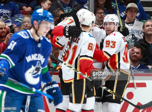 Troy Stecher of the Vancouver Canucks skates away dejected as Sam Bennett of the Calgary Flames celebrates a Calgary goal during their NHL game at...