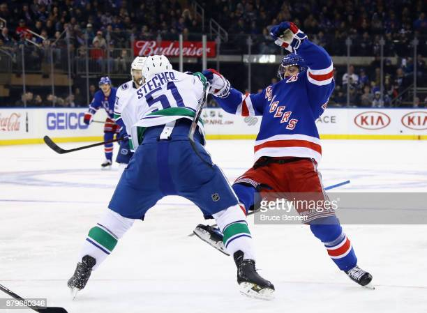 Troy Stecher of the Vancouver Canucks stands up Mats Zuccarello of the New York Rangers during the second period at Madison Square Garden on November...