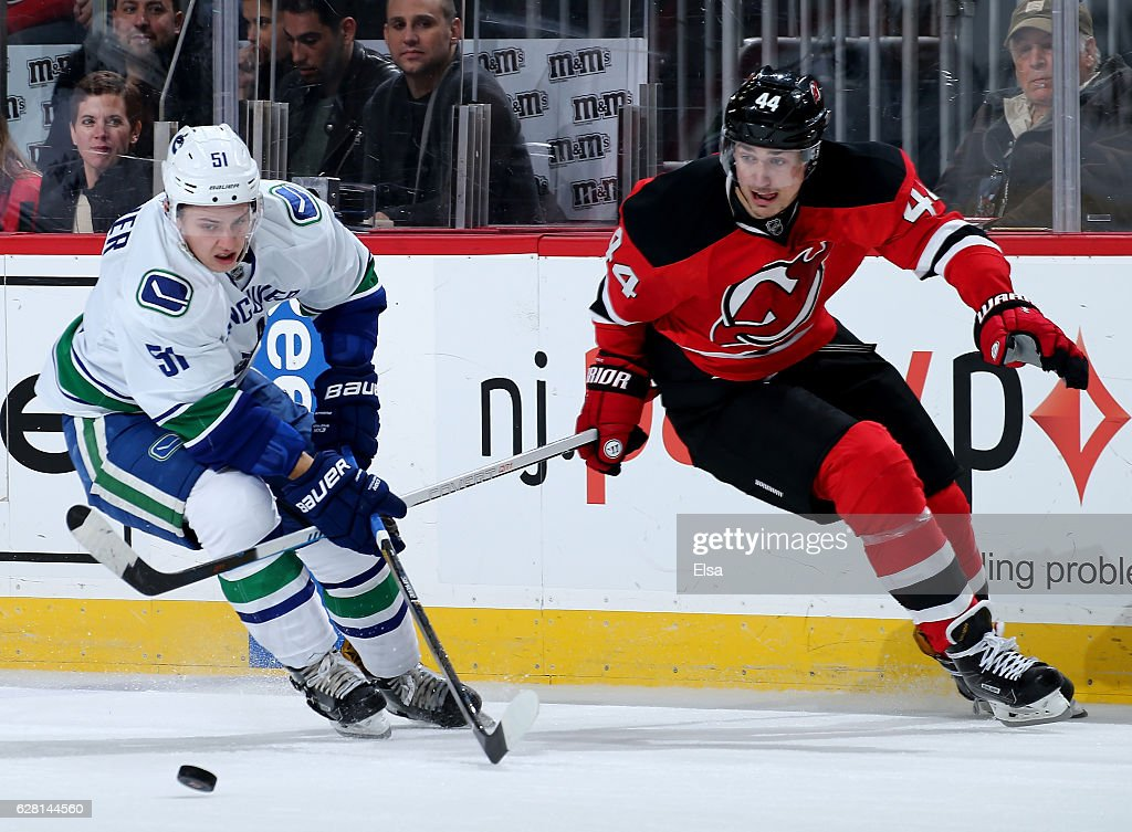 Troy Stecher #51 of the Vancouver Canucks takes the puck as Miles Wood #44 of the New Jersey Devils defends on December 6, 2016 at Prudential Center in Newark, New Jersey.