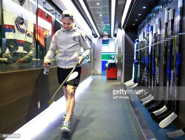 Troy Stecher of the Vancouver Canucks walks with his game sticks before their NHL game against the Winnipeg Jets at Rogers Arena October 12 2017 in...