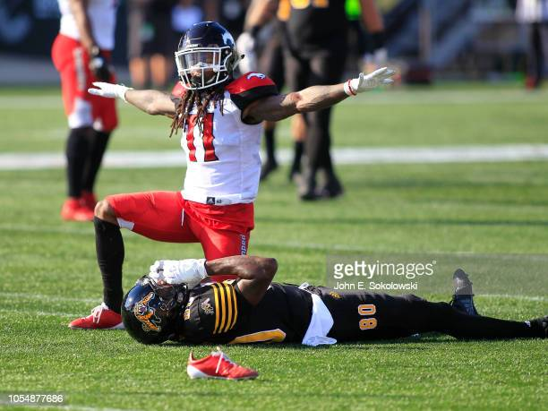 Troy Stoudermire of the Calgary Stampeders signals an incomplete pass as Hamilton Tiger-Cats Terrence Toliver lies on the turf during a game at Tim...