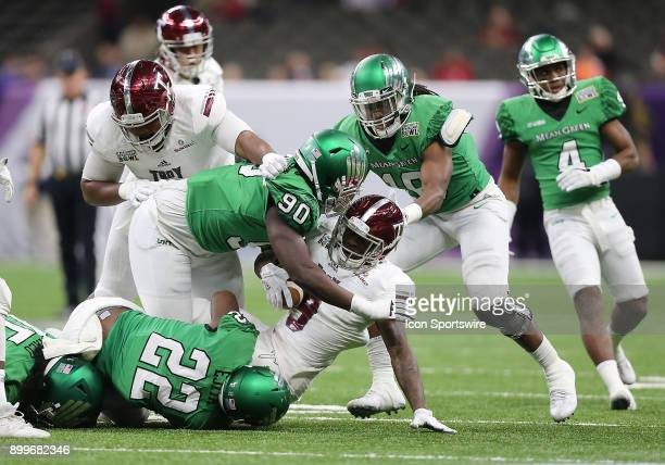 Troy Trojans cornerback Jalen Harris is tackled by North Texas Mean Green defensive end Tillman Johnson during a football game between the Troy...