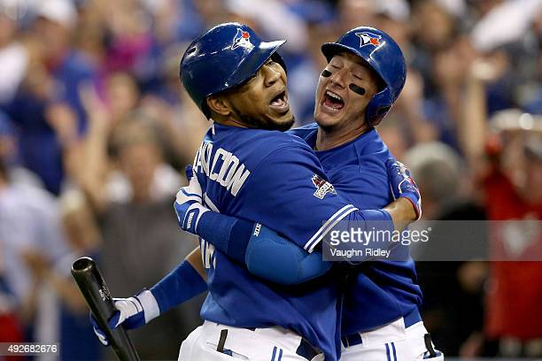 Troy Tulowitzki and Edwin Encarnacion of the Toronto Blue Jays celebrate after Encarnacion hits a sixth inning solo home run against the Texas...