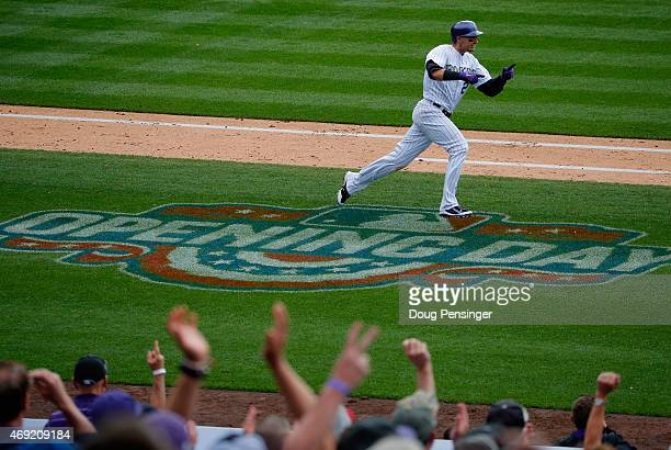 Troy Tulowitzki of the Colorado Rockies celebrates along with the fans as he runs to first base on his two RBI double off of Travis Wood of the...