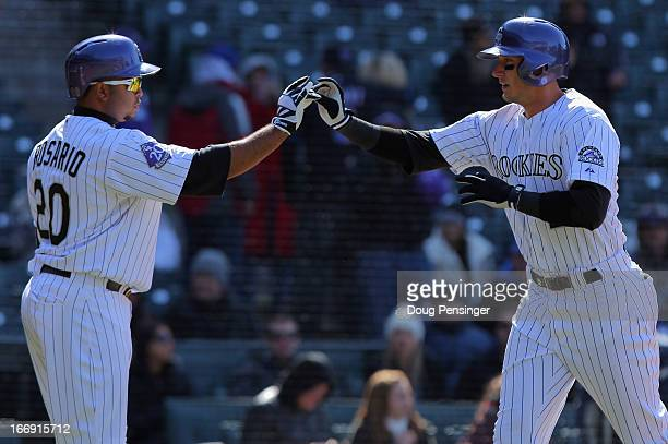 Troy Tulowitzki of the Colorado Rockies celebrates his solo homerun off of Jeremy Hefner of the New York Mets with Wilin Rosario of the Colorado...