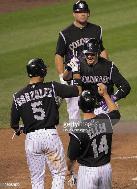 Troy Tulowitzki of the Colorado Rockies celebrates his three run homerun off of David Hernandez of the Arizona Diamondbacks with teammates Carlos...