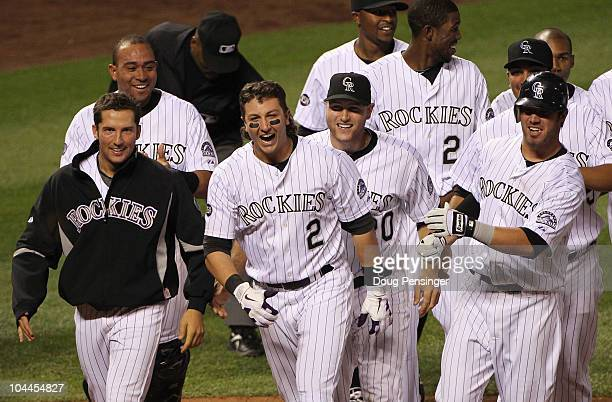Troy Tulowitzki of the Colorado Rockies celebrates with Huston Street and their teammates after he hit the game RBI double to score Carlos Gonzalez...