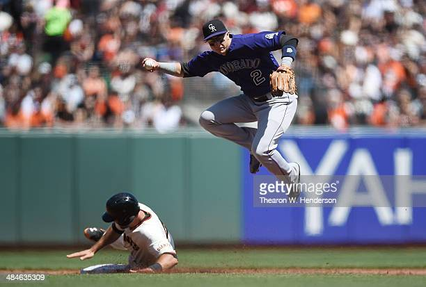 Troy Tulowitzki of the Colorado Rockies completes a double play after leaping over the sliding Brandon Hicks of the San Francisco Giants in the...