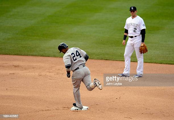 Troy Tulowitzki of the Colorado Rockies looks on as Robinson Cano of the New York Yankees rounds second base after his home run in the fifth inning...