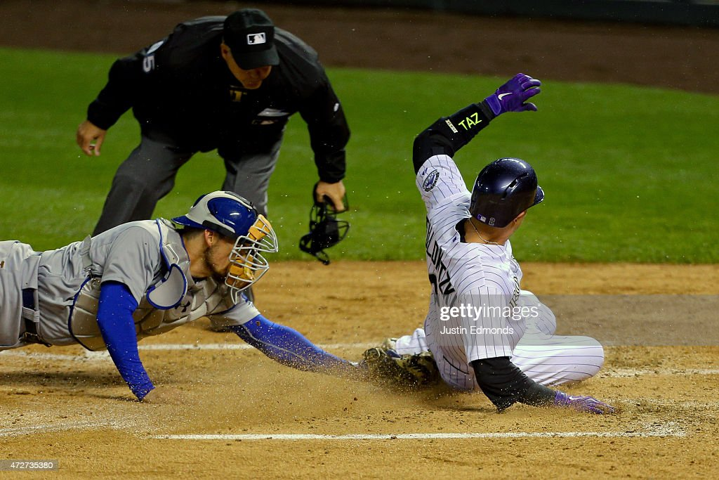 Troy Tulowitzki #2 of the Colorado Rockies slides in to score ahead of the tag by catcher Yasmani Grandal #9 of the Los Angeles Dodgers as home plate umpire Tim Timmons looks on during the fourth inning at Coors Field on May 8, 2015 in Denver, Colorado.