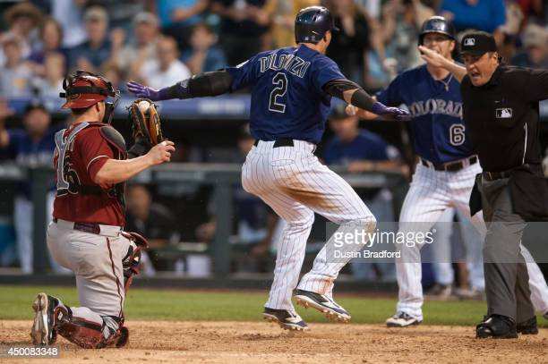Troy Tulowitzki of the Colorado Rockies slides safely into home past the tag attempt by Miguel Montero of the Arizona Diamondbacks as umpire Mike...