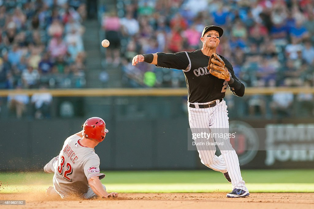 Troy Tulowitzki #2 of the Colorado Rockies throws to first base as he turns a double play past a sliding Jay Bruce #32 of the Cincinnati Reds in the fifth inning of a game at Coors Field on July 25, 2015 in Denver, Colorado.