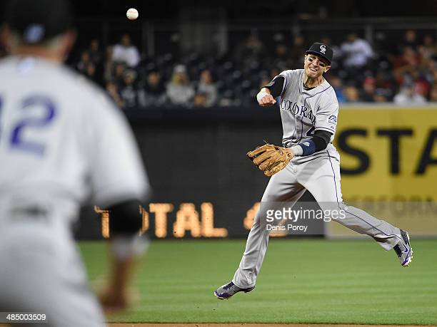 Troy Tulowitzki of the Colorado Rockies throws to first base to get the out on Nick Hundley of the San Diego Padres during the second inning of a...