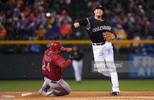 Troy Tulowitzki of the Colorado Rockies turns a successful double play over a sliding Chris Young of the Arizona Diamondbacks on a ball hit by...