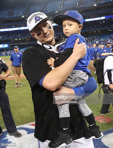 Troy Tulowitzki of the Toronto Blue Jays celebrates their series victory as he holds his son Taz Tulowitzki on the field following their MLB game...