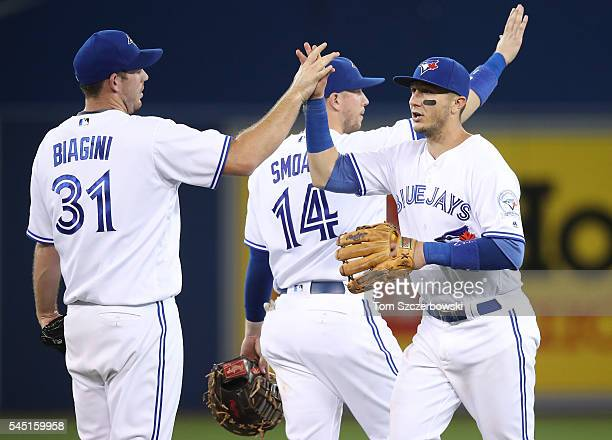 Troy Tulowitzki of the Toronto Blue Jays celebrates their victory with Joe Biagini during MLB game action against the Kansas City Royals on July 5...