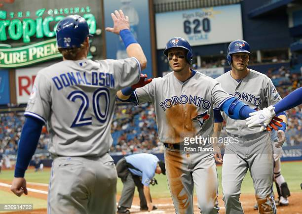 Troy Tulowitzki of the Toronto Blue Jays center celebrates with teammates Michael Saunders Josh Donaldson after hitting a threerun home run off of...