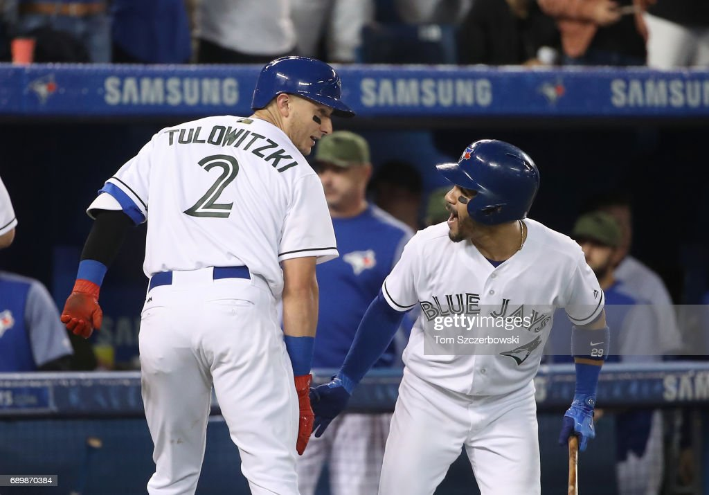 Troy Tulowitzki #2 of the Toronto Blue Jays is congratulated by Devon Travis #29 after hitting a grand slam home run in the third inning during MLB game action against the Cincinnati Reds at Rogers Centre on May 29, 2017 in Toronto, Canada.
