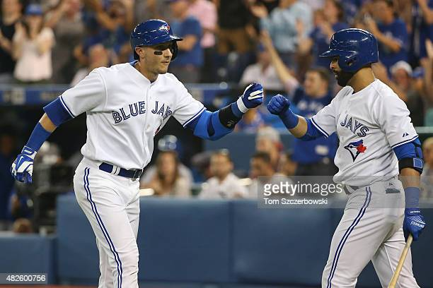 Troy Tulowitzki of the Toronto Blue Jays is congratulated by Jose Bautista after scoring a run in the seventh inning during MLB game action against...