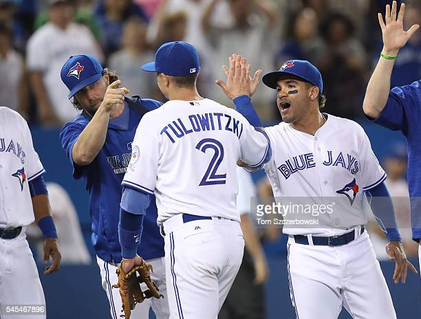 Troy Tulowitzki of the Toronto Blue Jays is congratulated by RA Dickey and Devon Travis during MLB game action against the Detroit Tigers on July 7...