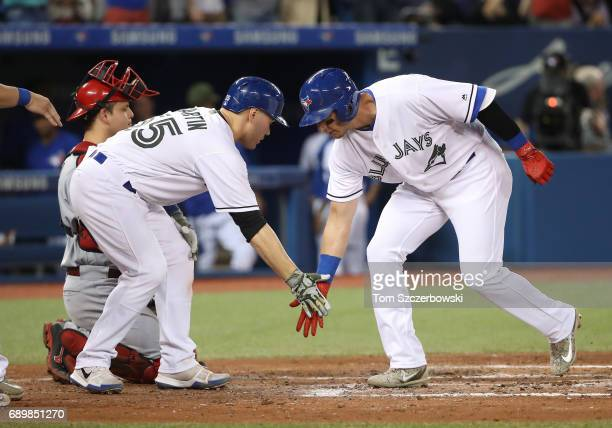 Troy Tulowitzki of the Toronto Blue Jays is congratulated by Russell Martin after hitting a grand slam home run in the third inning during MLB game...