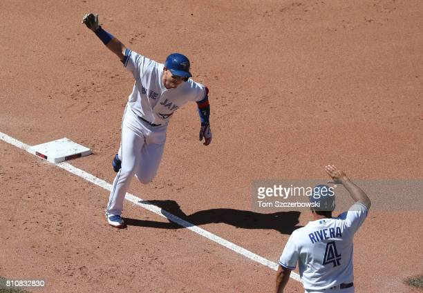 Troy Tulowitzki of the Toronto Blue Jays is congratulated by third base coach Luis Rivera as he circles the bases after hitting a threerun home run...