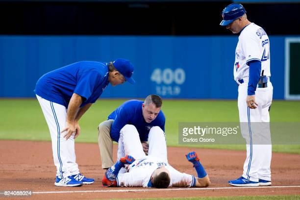 TORONTO ON JULY 28 Troy Tulowitzki of the Toronto Blue Jays is helped by Mike Frostad while manager John Gibbons and Derek Shelton look on during the...