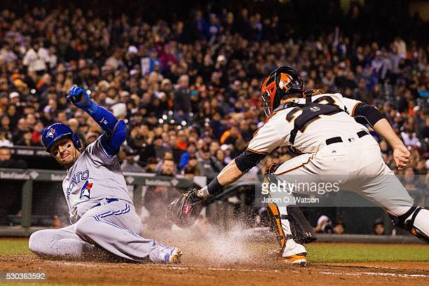 Troy Tulowitzki of the Toronto Blue Jays scores a run ahead of the tag from Buster Posey of the San Francisco Giants during the ninth inning at ATT...