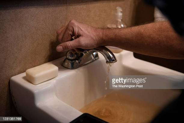 Troy Watts, a senior lead technician with John Moore Services, repairs a sink with brown tap water following an unprecedented winter storm that swept...