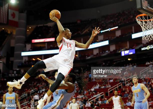 Troy Williams of the Houston Rockets drives to the basket and is fouled by Kenneth Faried of the Denver Nuggets in the first half at Toyota Center on...