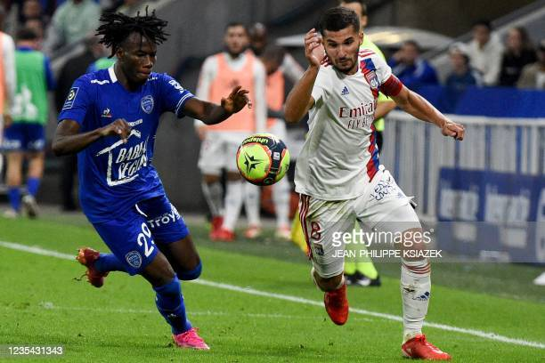 Troyes' Burkinabese defender Issa Kabore fights for the ball with Lyon's French midfielder Houssem Aouar during the French L1 football match between...