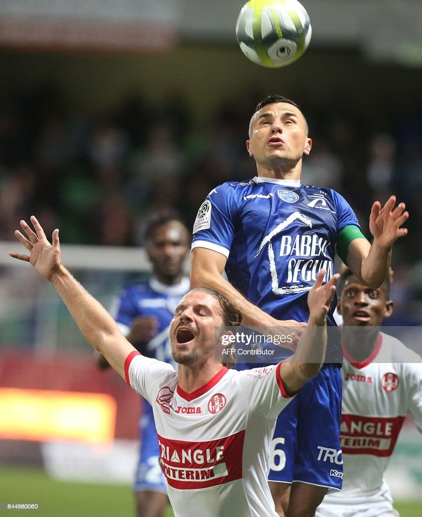 Troyes' French midfielder Karim Azamoum (up) vies with Toulouse's French midfielder Yannick Cahuzac (down) during the L1 football match between Troyes and Toulouse on September 9, 2017 at the Aube Stadium in Troyes. /
