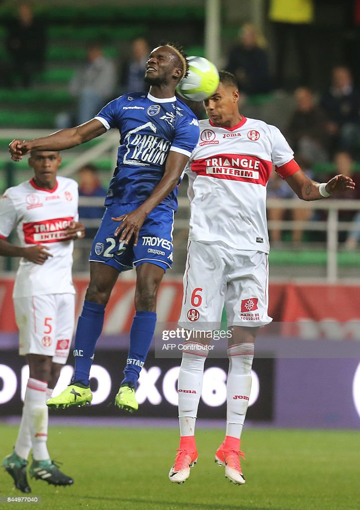 Troyes' Malian forward Adama Niane (L) vies with Toulouse's French defender Christopher Jullien (R) during the L1 football match between Troyes and Toulouse on September 9, 2017 at the Aube Stadium in Troyes. /