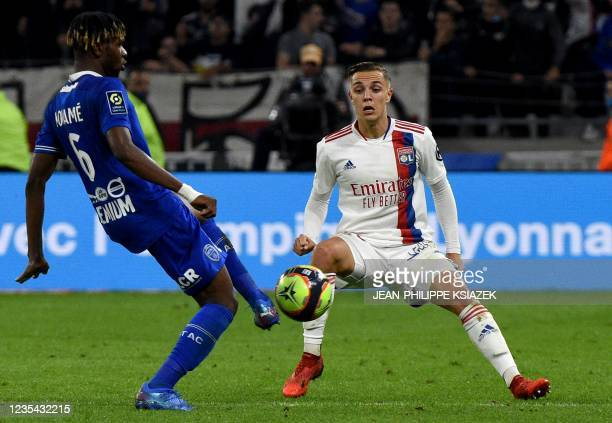 Troyes' Malian midfielder Rominigue Kouame fights for the ball with Lyon's French midfielder Maxence Caqueret during the French L1 football match...