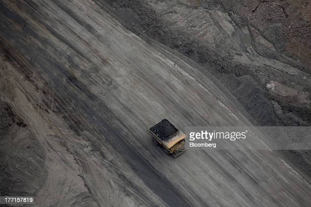 A truck carries oil sands at a Suncor Energy Inc oil sands mining operation Fort McMurray Alberta Canada on Tuesday Aug 13 2013 Canadian oil...
