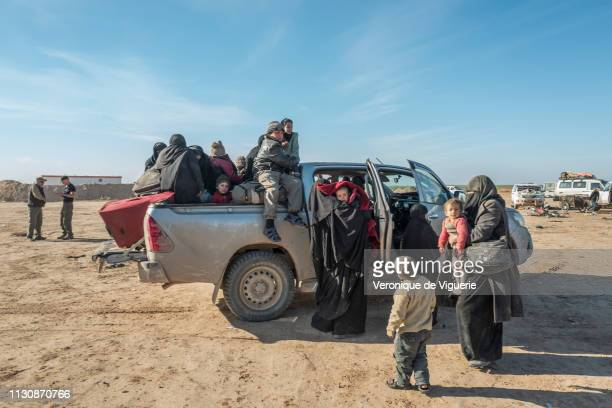 A truck carries women and children who just fled Baghouz the last Isis stronghold by crossing the desert in February 2019 south of Deir Ezzor Syria...