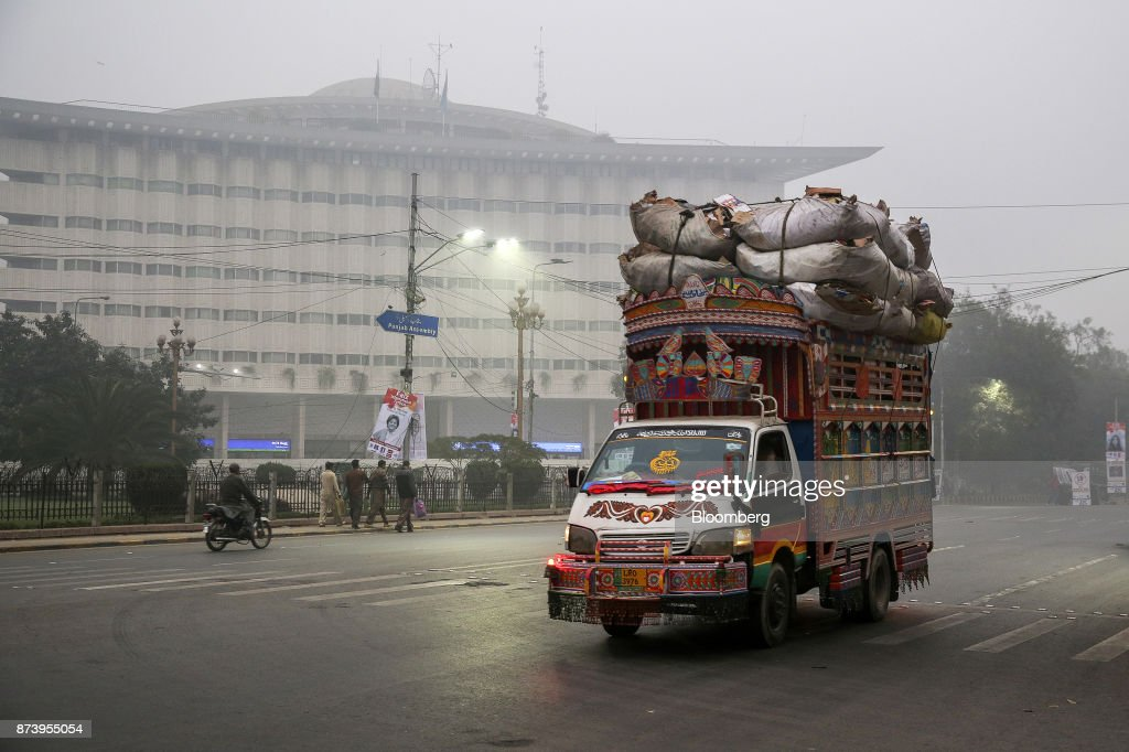 A truck carrying garbage passes the Water and Power Development Authority building shrouded in smog in Lahore Pakistan on Tuesday Nov 14 2017 The...
