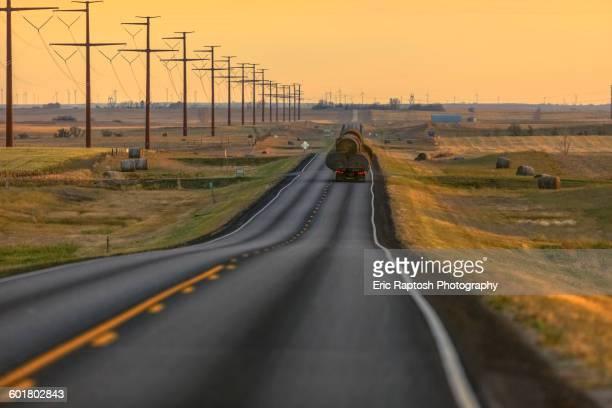 Truck carrying hay bales on rural highway