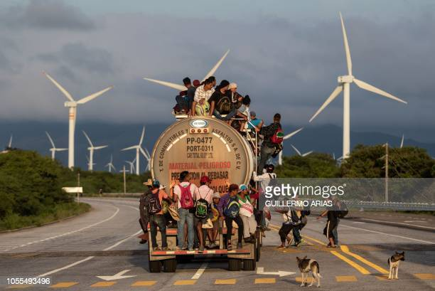 TOPSHOT A truck carrying mostly Honduran migrants taking part in a caravan heading to the US passes by a wind farm on their way from Santiago...