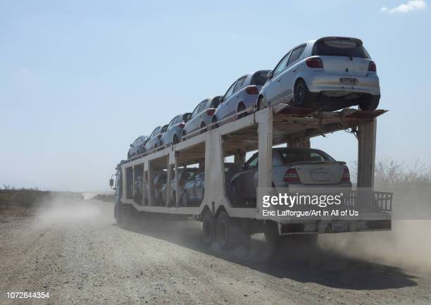 Truck carrying new cars coming from djibouti port on a dusty road, Oromia, Awash, Ethiopia on November 2, 2018 in Awash, Ethiopia.