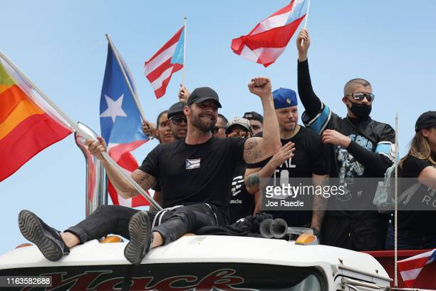 A truck carrying singer Ricky Martin Rapper Residente and Rapper Bad Bunny joins with thousands of other people as they fill the Expreso Las Américas...