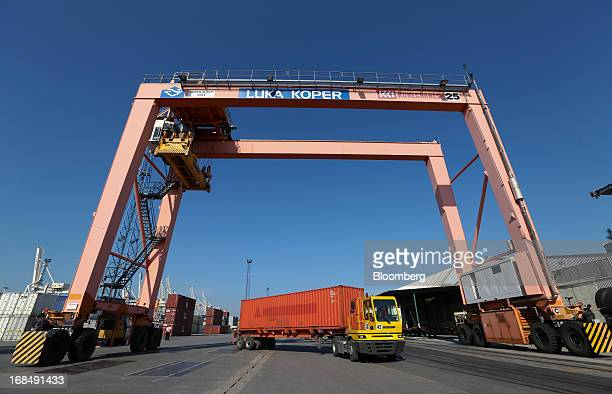 A truck collects a shipping container from the dockside at the port of Koper operated by Luka Koper dd in Koper Slovenia on Thursday May 9 2013 The...