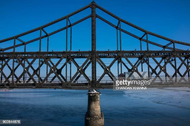 TOPSHOT A truck crosses the Friendship Bridge from the North Korean town of Sinuiju to the Chinese border city of Dandong in China's northeast...