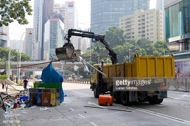 Truck dispose of material used to make barricades by pro-democracy 'Occupy Central' protesters that police just removed on Queensway, in Admirality...