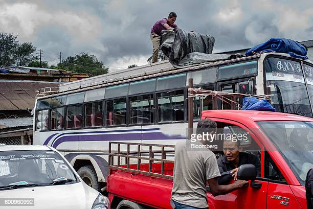 A truck driver covers luggage with a tarp on the roof of a bus in Shillong Meghalaya India on Friday Aug 12 2016 Two years of deficient rainfall have...