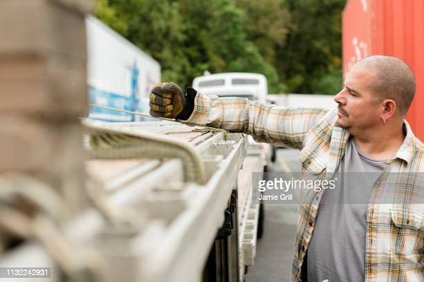 truck driver fastening wood planks to his semi-truck - strap stock pictures, royalty-free photos & images