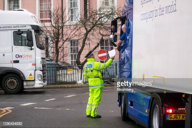 Truck driver hands over paperwork to a policeman before entering the Port of Dover Ltd. In Dover, U.K., on Tuesday, Jan. 5, 2021. The lack of chaos...