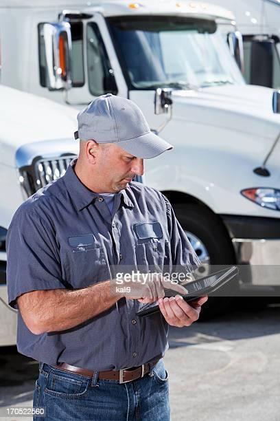 Chauffeur routier en face de big les mannequins avec Tablette numérique