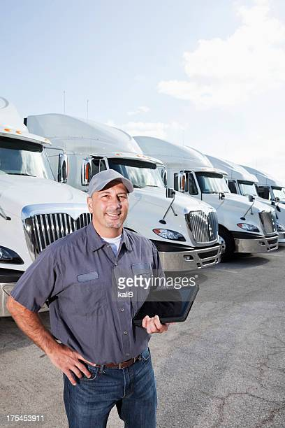 truck driver in front of big rigs with digital tablet - convoy stock pictures, royalty-free photos & images