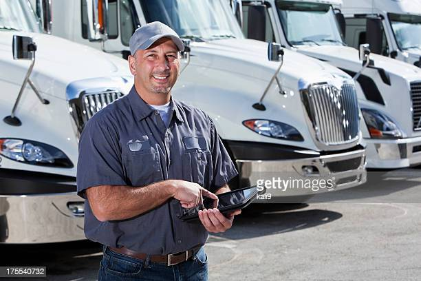 Truck driver in front of big rigs with digital tablet